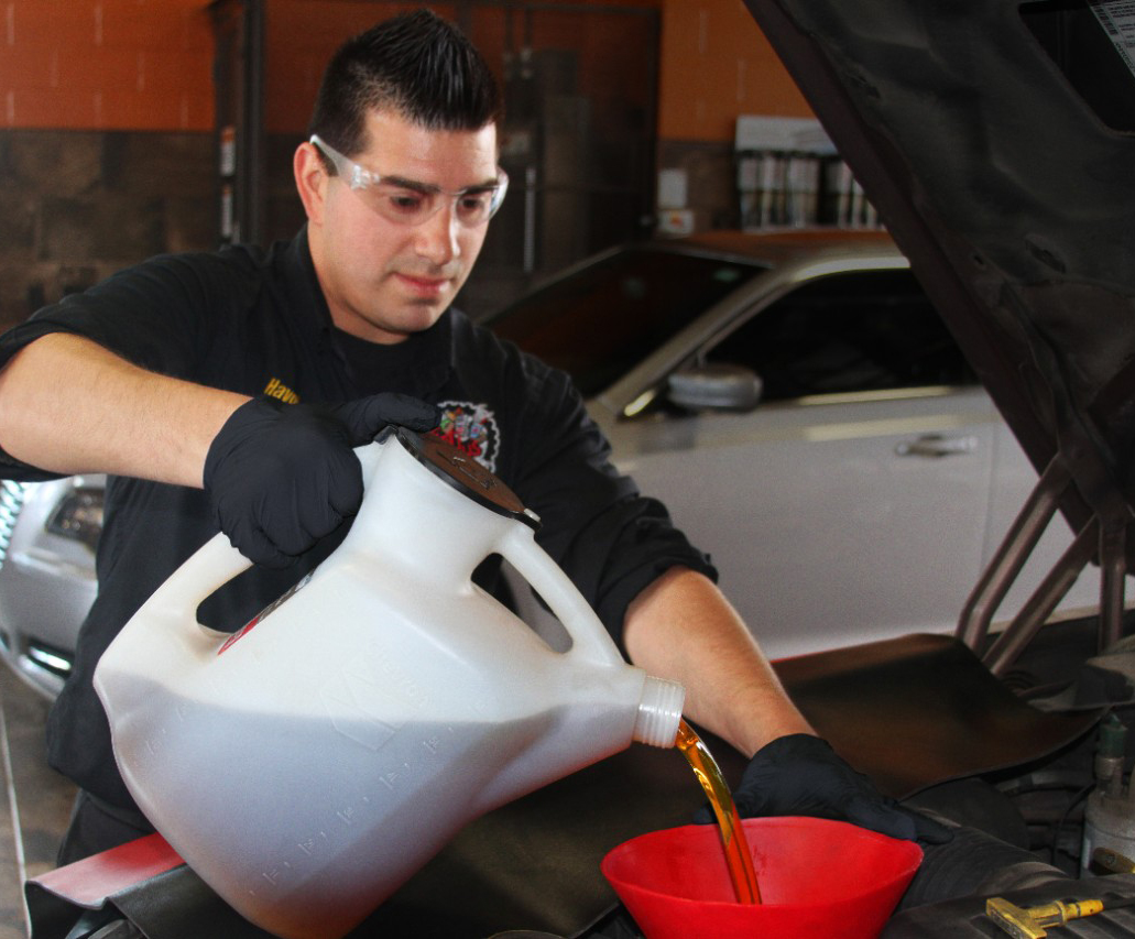 Havoline pro pouring oil into vehicle